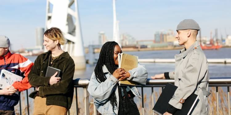 4 young students standing with their backs to the river thames, smiling and holding sketch books. The student in the centre of the image is holding a sketchbook up to her face and laughing.
