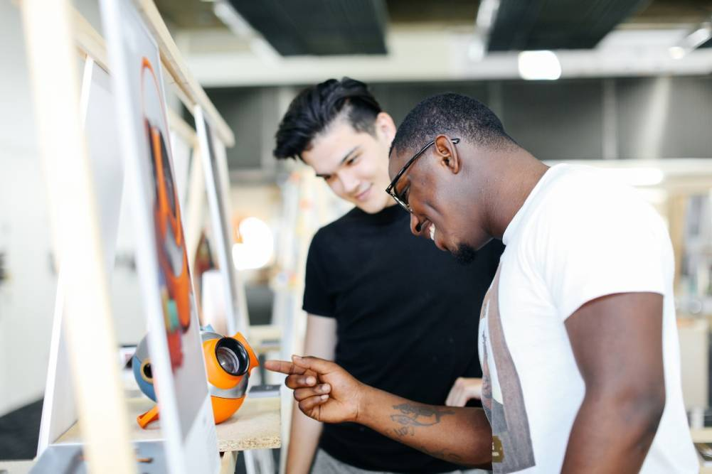 Two male students explore the work on display at an open day